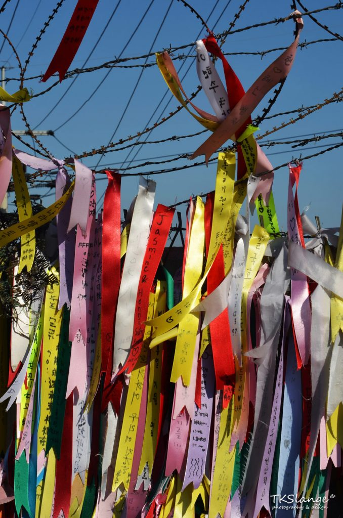 Vanes with wishes of freedom and reunification are tied to the fence of the civilian border.