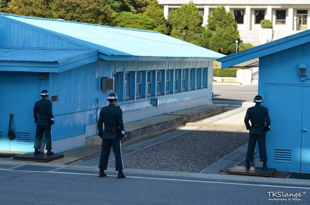 ROK soldiers facing North Korea. In the doorway of the building across stands a North Korean soldier with binoculars.