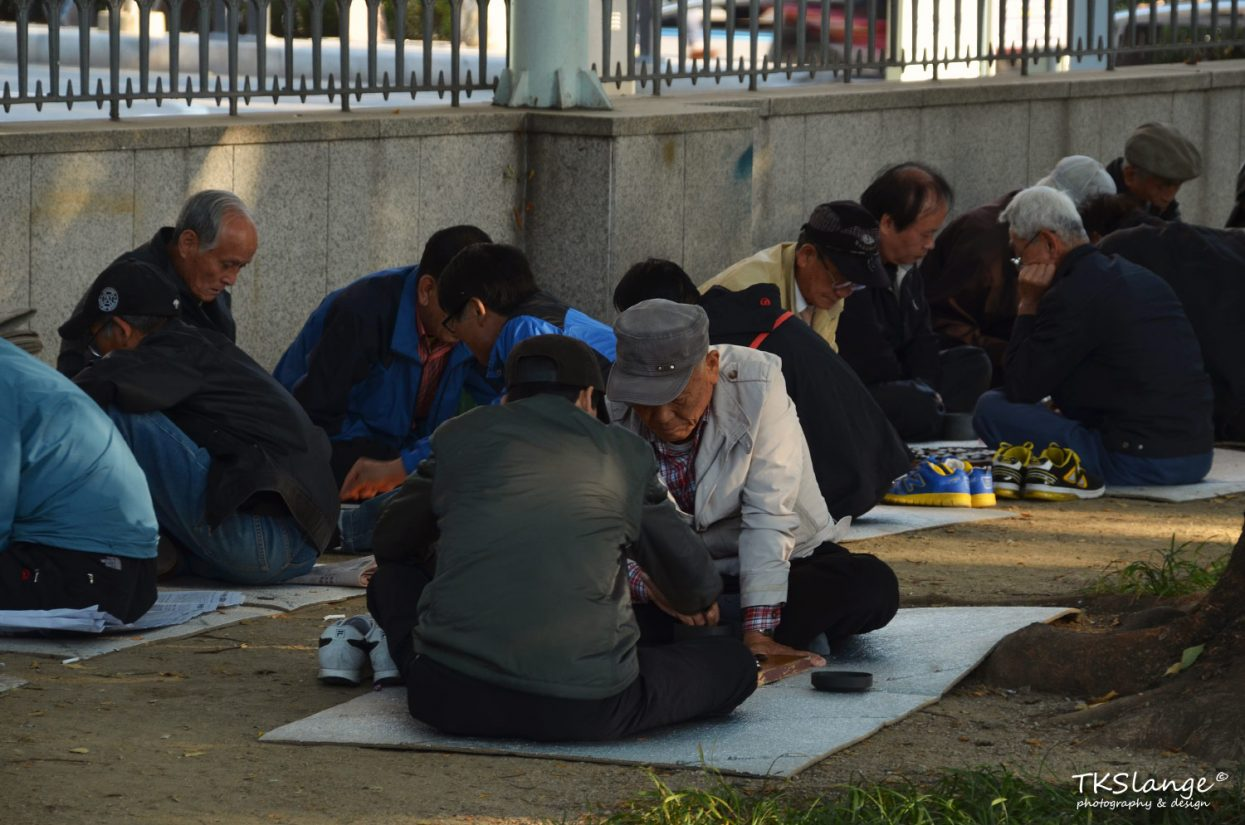 Retired men playing board games at Jongmyo Park.