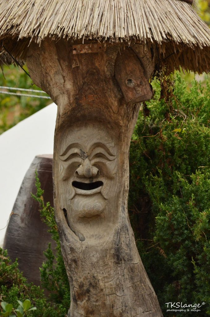 A traditional Korean mask carved in a tree (as a mailbox?)